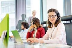 Stående av att le kundtjänstrepresentanten genom att använda bärbara datorn medan kollegor i bakgrund på kontoret Arkivfoto