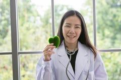 Stående av att le kvinnadoktorn med grön hjärta Vänlig ung kvinnlig doktor med en stetoskop omkring på hals asiatiskt folk royaltyfri bild