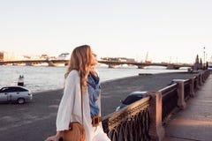 Stående av att le kvinnan i en vit kofta Skratta flickan på bakgrunden av gatan royaltyfria foton