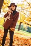 Stående av att le kvinnan med hunden utomhus i höst arkivbilder