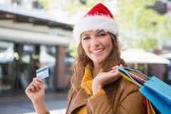 Stående av att le kvinnan med santa hatt- och shoppingpåsar Royaltyfria Bilder