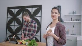 Stående av att le kvinnan på kokkonst, lyckliga kvinnliga blickar på mannen som förbereder sund mat från grönsaker för användbart arkivfilmer