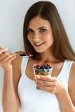 Stående av att le kvinnan som äter yoghurt med havre och bär royaltyfria foton