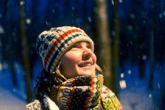 Stående av att le kvinnan som ser upp i luva i aftonvinterskog royaltyfria bilder
