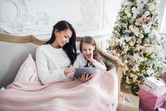 Stående av att le litet dottersammanträde samman med hennes moder och att använda den digitala minnestavlan hemma på jultid arkivfoton