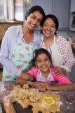 Stående av att le mång--utveckling familjanseende vid deg i kök arkivfoto