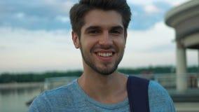 Stående av att le mannen som poserar på kamera i utomhus- lager videofilmer