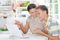 Stående av att le modern och sonen som använder bärbara datorn arkivfoton