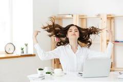 Stående av att le nätt ungt sammanträde för affärskvinna på arbetsplats royaltyfri foto