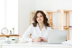 Stående av att le nätt ungt sammanträde för affärskvinna på arbetsplats royaltyfria foton