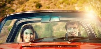 Stående av att le par i röd cabriolet arkivfoto