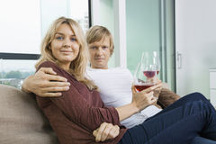 Stående av att le par med vinexponeringsglas i vardagsrum hemma Arkivfoton