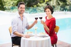 Stående av att le par som rostar rött vin Royaltyfri Bild