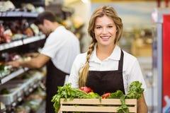 Stående av att le personalkvinnan som rymmer en ask med nya grönsaker Royaltyfria Foton