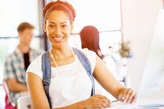 Stående av att le sammanträde för afro--amerikan kontorsarbetare i offfice Fotografering för Bildbyråer