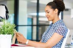 Stående av att le sammanträde för afro--amerikan kontorsarbetare i offfice Royaltyfri Fotografi