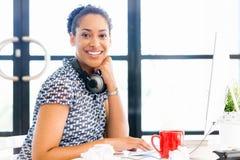 Stående av att le sammanträde för afro--amerikan kontorsarbetare i offfice Arkivfoto