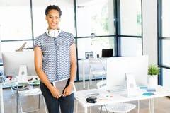 Stående av att le sammanträde för afro--amerikan kontorsarbetare i offfice Royaltyfria Bilder