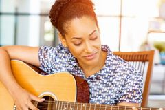 Stående av att le sammanträde för afro--amerikan kontorsarbetare i offfice med gitarren Arkivfoton