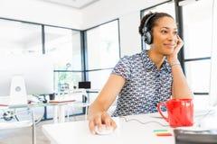 Stående av att le sammanträde för afro--amerikan kontorsarbetare i offfice med hörlurar Fotografering för Bildbyråer