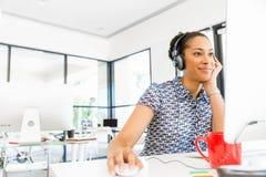 Stående av att le sammanträde för afro--amerikan kontorsarbetare i offfice med hörlurar Royaltyfria Bilder