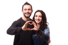 Stående av att le skönhetflickan och hennes stiliga pojkvändanandeform av hjärta vid deras händer Arkivfoto