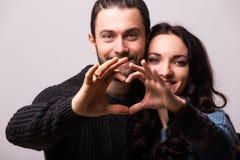 Stående av att le skönhetflickan och hennes stiliga pojkvändanandeform av hjärta vid deras händer Royaltyfria Bilder