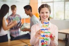 Stående av att le skolflickan som undersöker molekylmodellen i laboratorium Arkivfoto