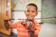 Stående av att le skolpojken som spelar fiolen i klassrum arkivfoto