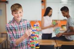 Stående av att le skolpojken som undersöker molekylmodellen i laboratorium Arkivbild