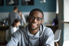 Stående av att le svarta mannen som ser kameran i kafé royaltyfri fotografi