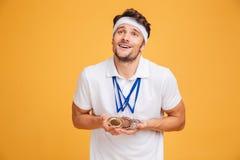Stående av att le ung spotrsman med tre medaljer Arkivbild