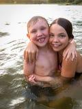 Stående av att le unga barn pojke och flicka som ger en kram i vattendet fria arkivbild