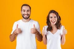 Stående av att le upp den folkmannen och kvinnan i grundläggande bekläda visande tummar, medan stå tillsammans isolerat över guli arkivfoton