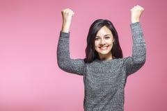 Stående av att segra den lyckade unga affärskvinnan, lyckligt extatiskt fira vara vinnare, på rosa bakgrund Positiv royaltyfri bild