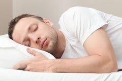 Stående av att sova den unga mannen i vit fotografering för bildbyråer
