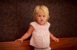 stående av att stå den lilla blonda flickan i rosa färger mot den bruna väggen Arkivbild