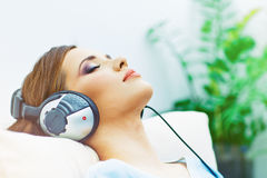 Stående av att vila den unga kvinnan hemma med lyssnande musik Royaltyfria Bilder
