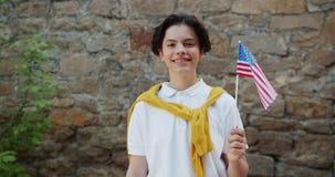 Stående av attraktiv amerikansk det fria för tonårs- pojke med att le för USA-flagga stock video
