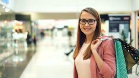 Stående av attraktiva bärande exponeringsglas för ung kvinna och trendiga plagg som ser kameran som rymmer påsestund lager videofilmer