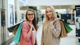 Stående av attraktiva unga damer med pappers- påsar som står i shoppinggallerian som rymmer köp och ser kameran stock video