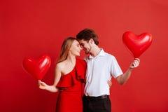 Stående av attraktiva unga par som poserar på röd bakgrund och rymmer ballonghjärta royaltyfri fotografi