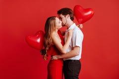 Stående av attraktiva unga par som poserar på röd bakgrund och rymmer ballonghjärta arkivbild