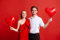 Stående av attraktiva unga par som poserar på röd bakgrund och rymmer ballonghjärta fotografering för bildbyråer