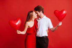 Stående av attraktiva unga par som poserar på röd bakgrund och rymmer ballonghjärta royaltyfria bilder