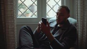 Stående av attraktivt mansammanträde i fåtölj i vardagsrum och användasmartphone Stilfull affärsmanbläddrandeinternet arkivfilmer