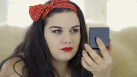 Stående av attraktivt ungt plus formatflickan som gör sminket som ser i spegelnärbilden Fyllig kvinna som målar hennes kanter lager videofilmer