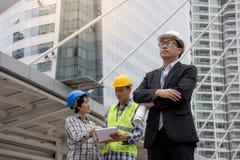 Stående av bärande arkitekter för en säkerhetshjälm för asiatisk allvarlig tekniker som diskuterar konstruktionsplan Arkivfoton