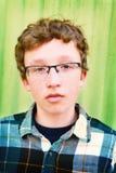 Stående av bärande exponeringsglas för en tonårs- pojke mot en grön metallbyggnad Fotografering för Bildbyråer