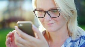 Stående av bärande exponeringsglas för en ung kvinna som tycker om en smartphone i parkera Härlig solilsken blick arkivbilder